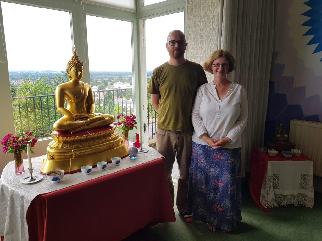 Kaspa and Satya are standing next to the shrine, on which there is a seated golden coloured Buddha statue.