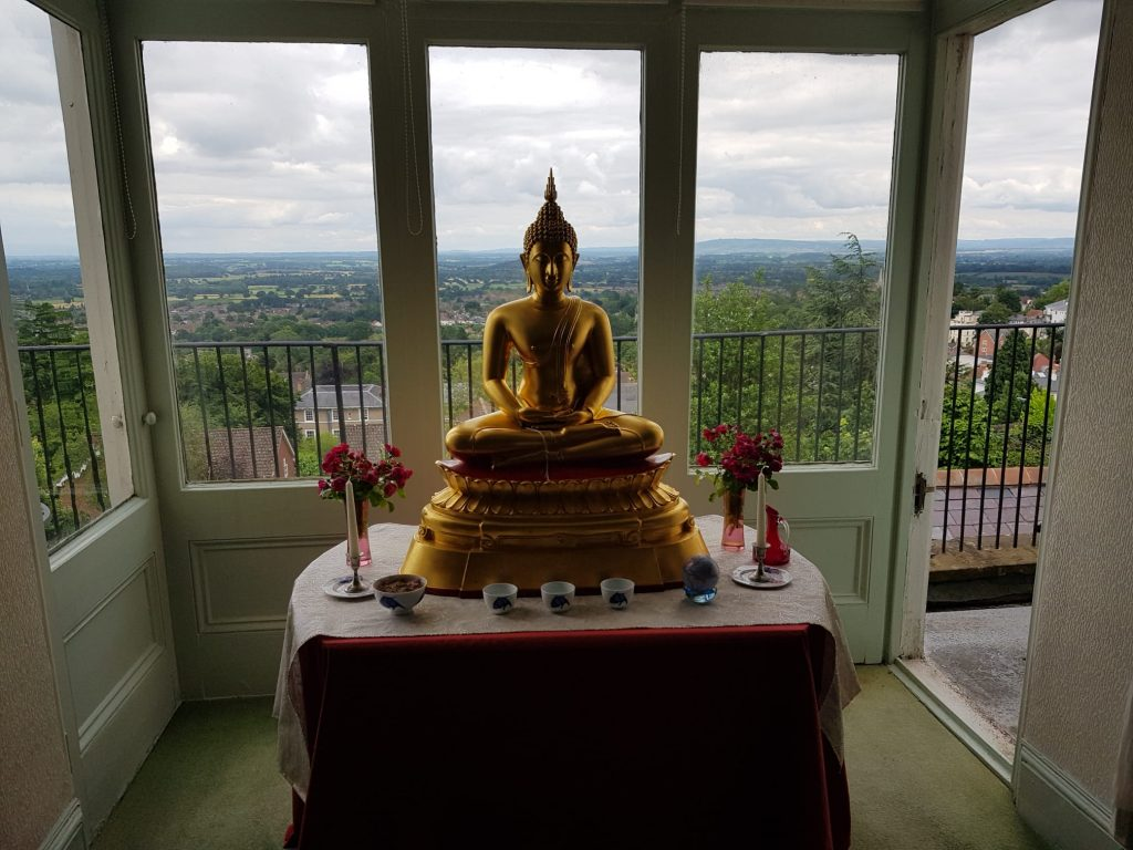 a golden Buddha statue sits on a shrine in front of tall windows looking out over countryside